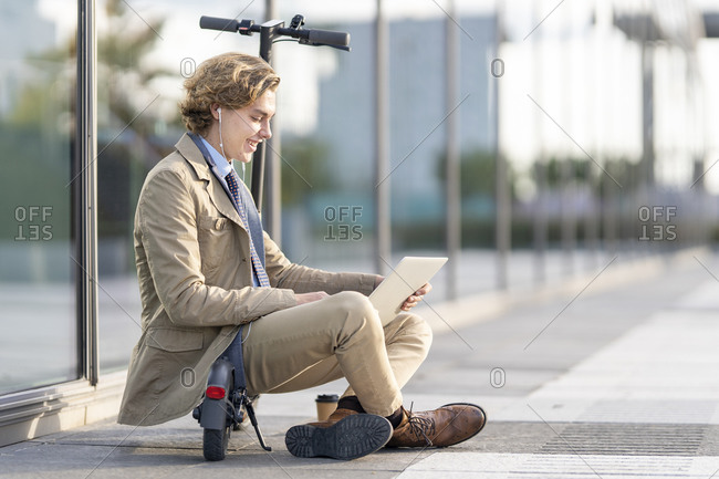 Businessman wearing in-ear headphones using laptop while sitting on electric push scooter