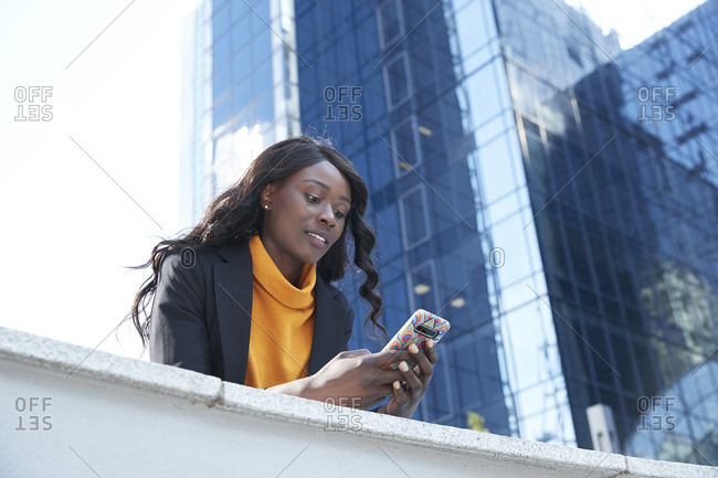 Businesswoman using mobile phone while leaning on retaining wall against office building
