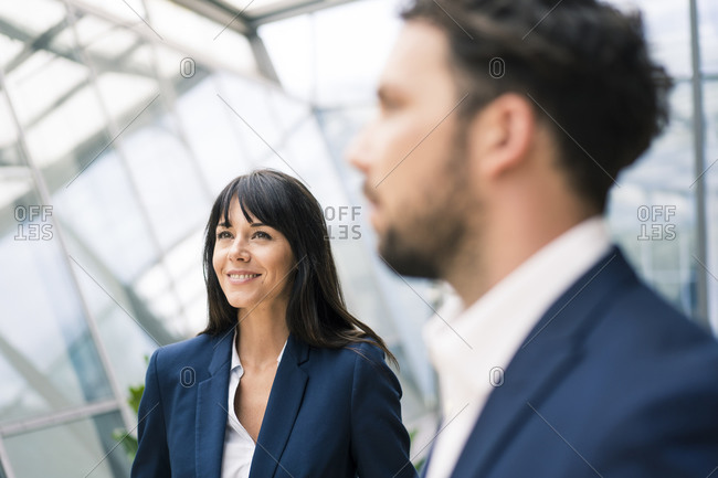 Smiling businesswoman standing by male colleague looking away in office during meeting