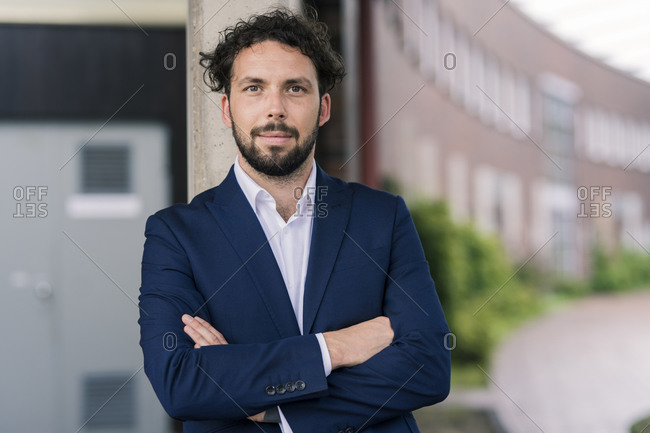 Confident male professional with arms crossed standing against building at office park