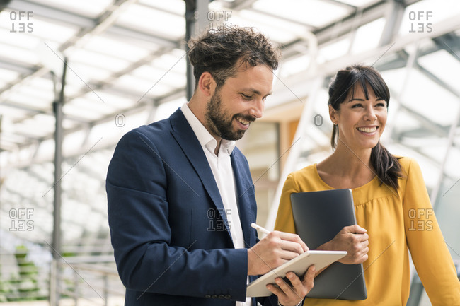 Smiling male colleague using digital tablet standing by female entrepreneur at office