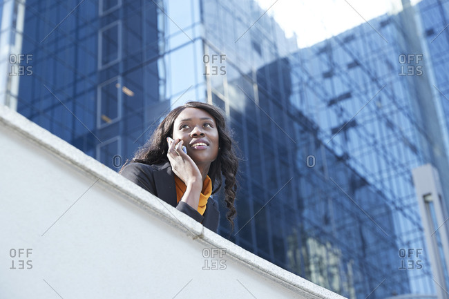 Smiling businesswoman on phone call leaning on retaining wall against office building