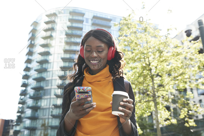 Smiling female professional with disposable coffee cup listening music at office park