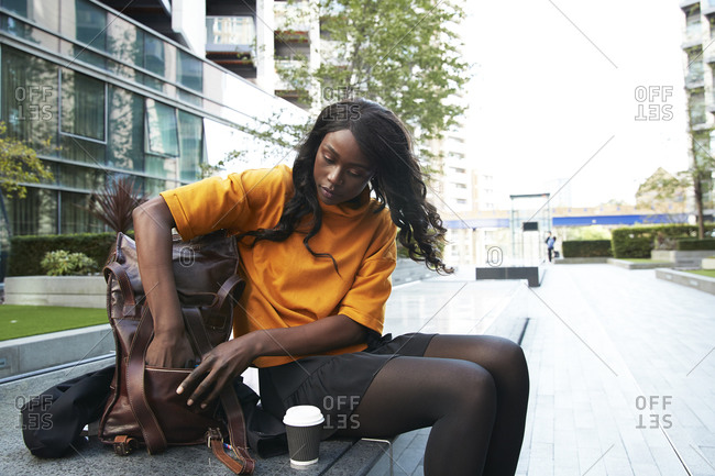 Businesswoman with disposable coffee cup finding something in backpack at office park