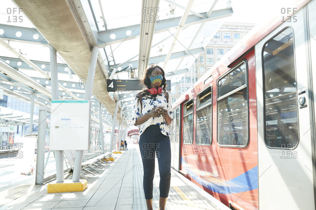 Businesswoman wearing face mask using mobile phone while standing at station platform