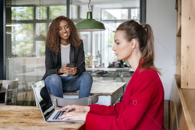 Young businesswoman looking at colleague while working on laptop in office cafeteria