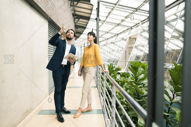 Male entrepreneur pointing while female colleague standing by in corridor of office