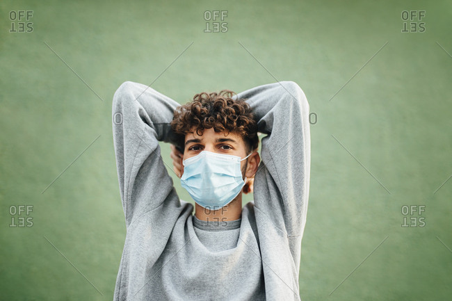 Caucasian man with hands behind head wearing surgical mask against green background