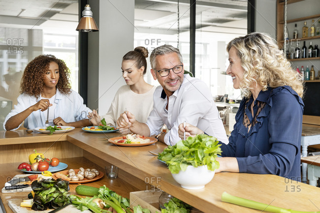 Smiling businessman looking at female colleague while having food in office kitchen