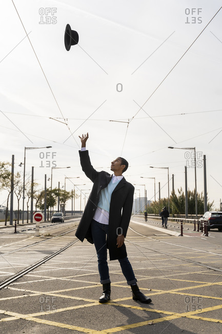 Fashionable young man throwing hat while standing on street between railroad track