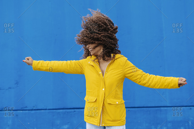 Playful woman with arms outstretched tossing hair while standing against blue wall