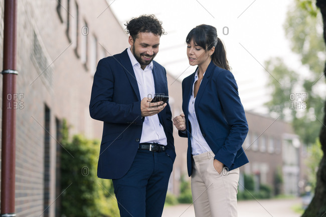 Businessman using smart phone standing by female colleague standing in office park