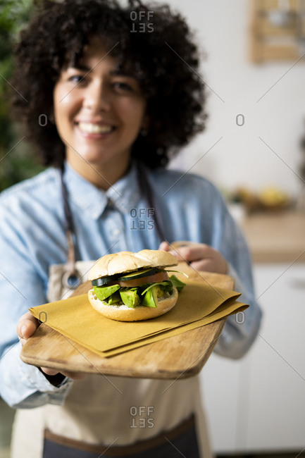 Young woman holding freshly made vegan sandwich with cucumber- avocado and tomato