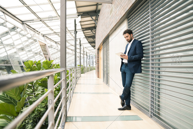 Businessman using digital tablet while leaning against wall in corridor at office