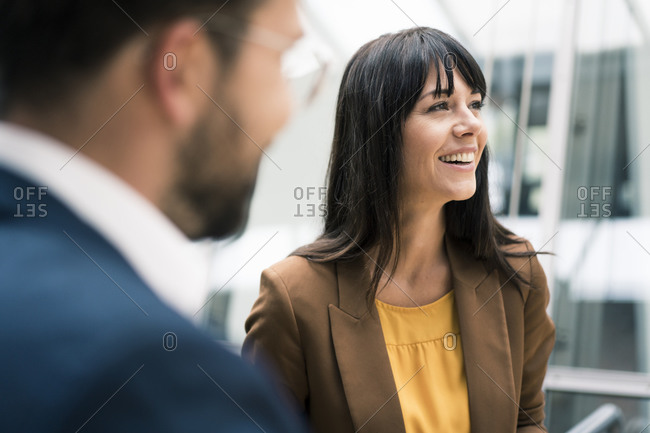 Happy female entrepreneur looking away while standing by male colleague in office