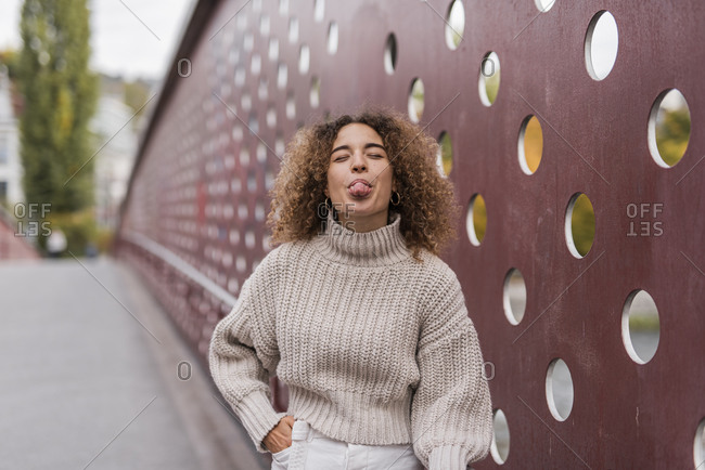 Playful young Afro woman sticking out tongue while standing against metallic wall