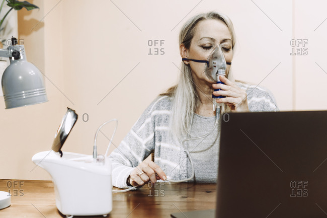 Senior woman with eyes closed using nebulizer during online consultation at home