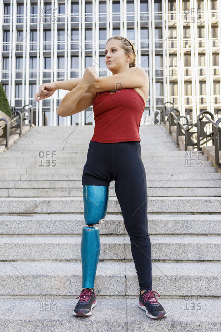 Young sportswoman with prosthetic leg stretching while standing on steps in city