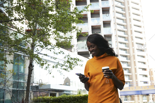 Happy businesswoman with disposable coffee cup using smart phone at office park