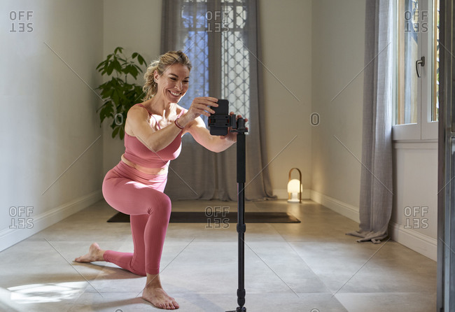 Happy female yoga instructor preparing mobile phone for online lessons at home