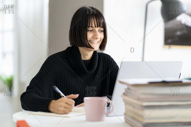 Smiling young female student with laptop writing while studying in study room