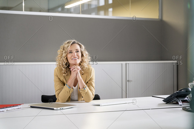 Smiling female professional with hands clasped day dreaming at desk in office