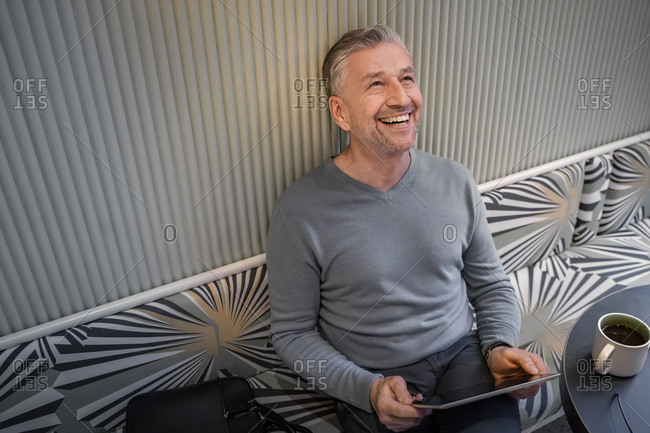 Happy businessman with digital tablet looking up while sitting at modern cafe