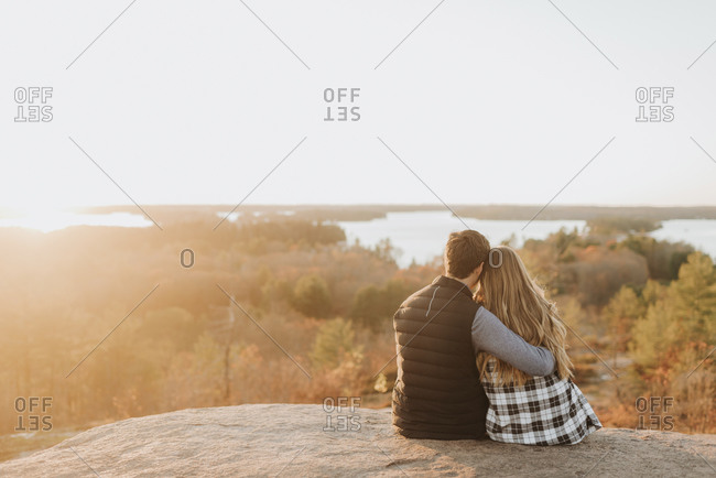 Young couple sitting together on rocky surface admiring setting sun in autumn