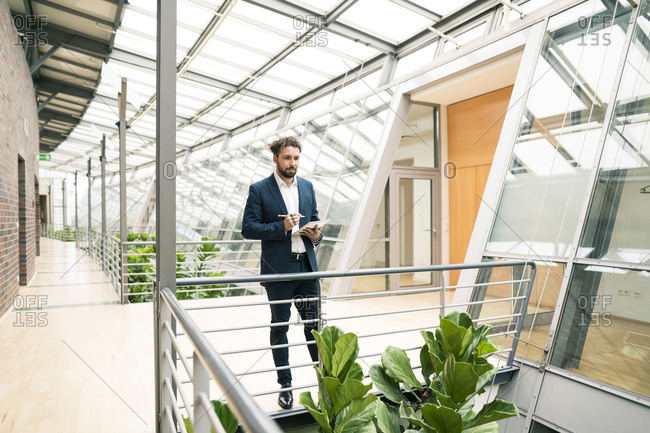Male entrepreneur with digital tablet looking at plant in corridor of office