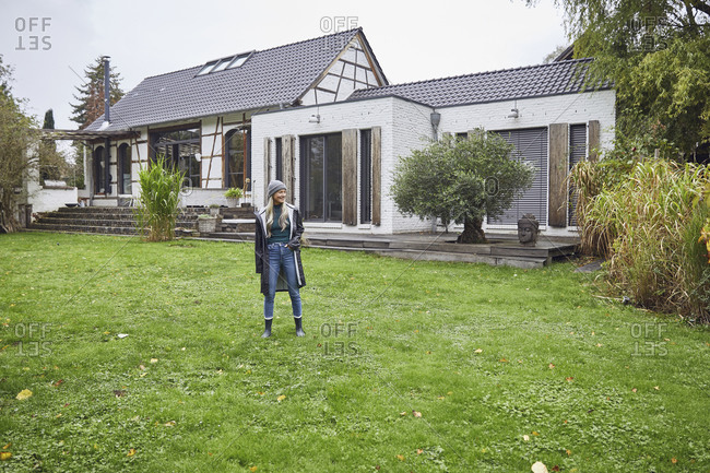Mature woman with hands in pockets standing on grass against built structure