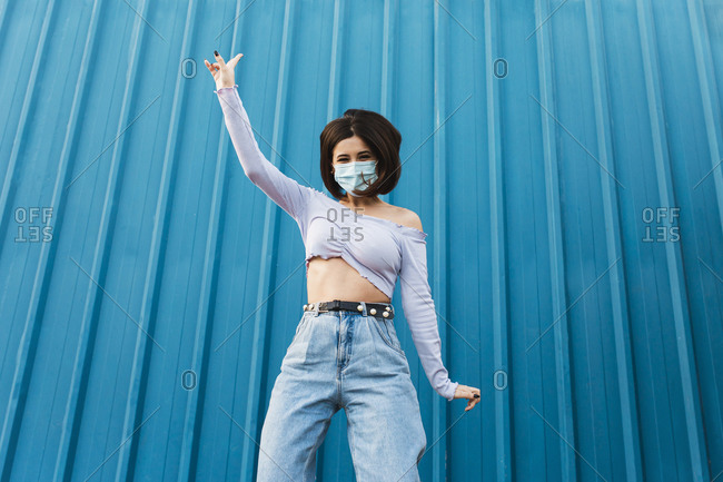 Carefree woman wearing face mask standing with hand raised against blue wall