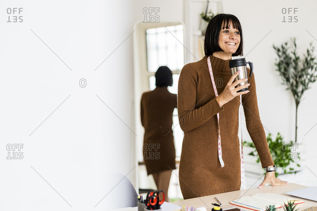 Happy young female stylist day dreaming while holding coffee cup in atelier