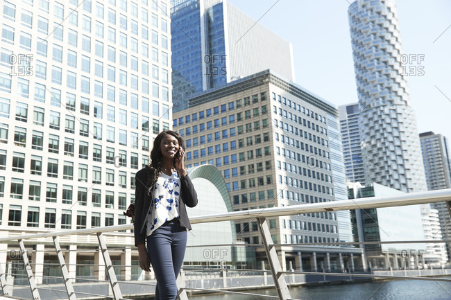 Smiling businesswoman talking on call while walking by railing on sunny day
