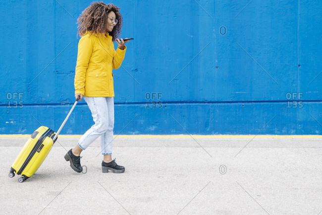 Woman with luggage talking on mobile phone while walking against blue wall