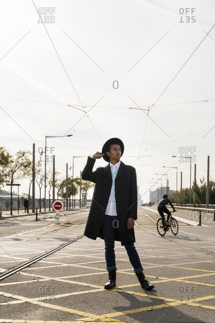Young man looking away while holding hat between railroad track on street