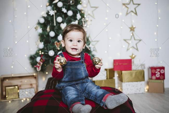 Happy baby boy playing with bauble while sitting at home during Christmas