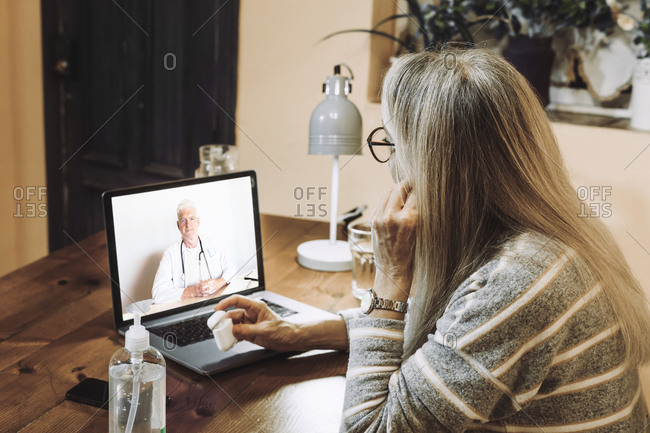 Senior patient taking advice of male doctor on video call during COVID-19