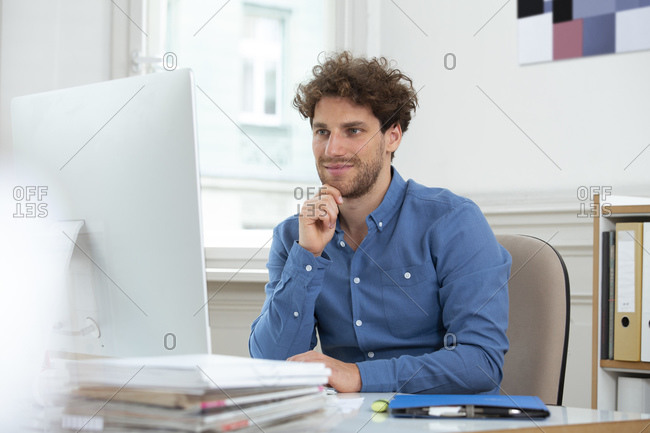 Male professional with hand on chin working over computer in office cabin