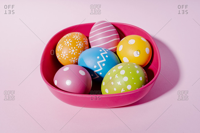 Variation design on colorful Easter eggs in red bowl on purple background