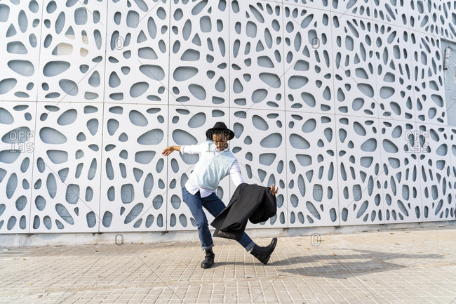 Carefree young man dancing on sidewalk against pattern wall on sunny day
