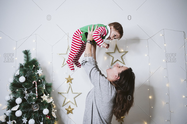 Smiling woman picking up baby boy while playing at home during Christmas