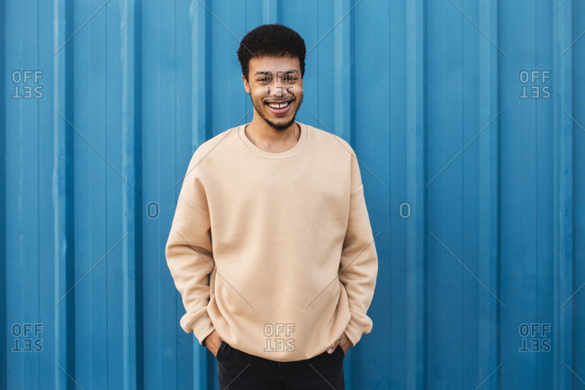 Young man with hands in pockets smiling while standing against blue wall