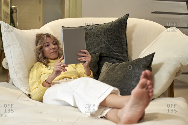Mature woman lying on lounge chair while checking digital tablet at home