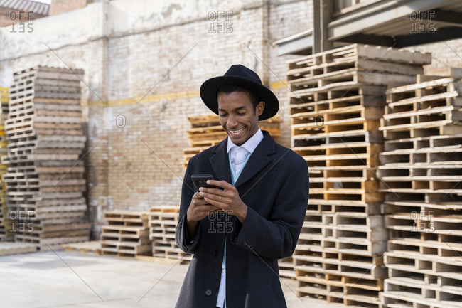 Young man in hat using mobile phone while standing against wood pallets