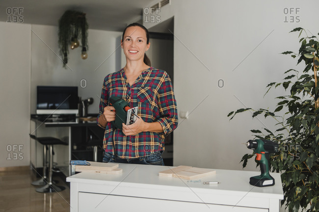 Mid adult woman holding electric jigsaw while standing by table at home