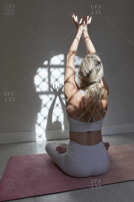Mature woman with hands raised practicing yoga in exercise room at home