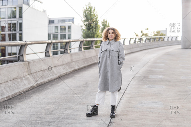 Beautiful young woman with curly blond hair standing on bridge in city