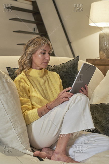Mature woman using digital tablet while siting on lounge chair at home