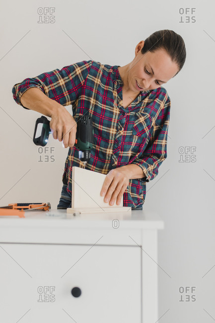 Mid adult woman using electric drill while working by cabinet at home