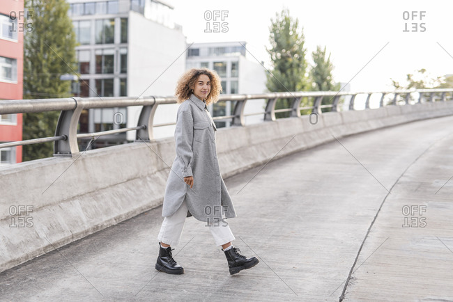 Beautiful young woman with curly blond hair walking on bridge in city